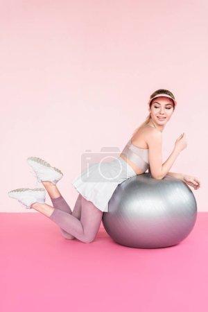 cheerful sportswoman in visor hat posing near grey fitness ball on pink