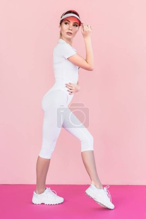 sportswoman in visor hat looking away and posing on pink
