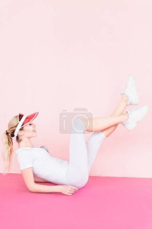 side view of happy female athlete in visor hat exercising on pink