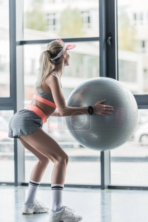 Photo for Rear view of sporty girl in visor hat exercising with fitness ball at gym - Royalty Free Image