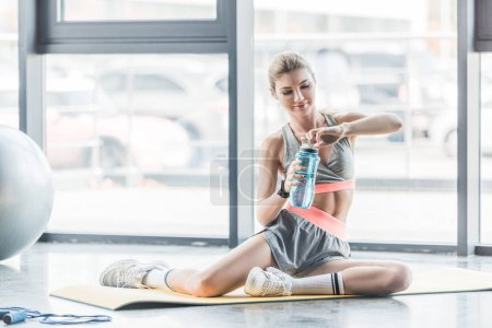 Photo for Happy female athlete with smartwatch resting with sport bottle of water on fitness mat at gym - Royalty Free Image