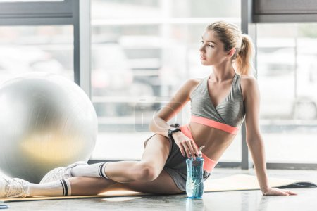 selective focus of sporty woman with smartwatch resting with sport bottle of water near fitness ball at gym
