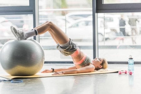 side view of young female athlete doing exercise with fitness ball at gym