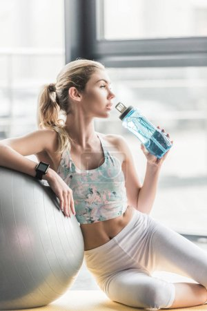 attractive female athlete with smartwatch resting and drinking water near fitness ball at gym