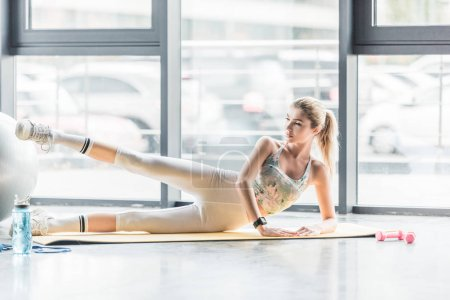 young sportswoman doing exercise on fitness mat at gym