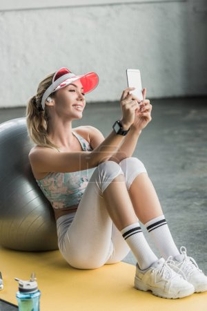 happy female athlete with smartwatch taking selfie on smartphone near fitness ball at gym