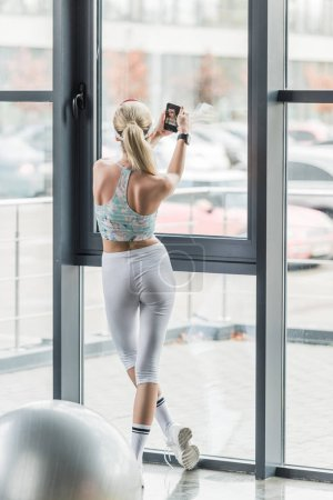 back view of female athlete with smartwatch taking selfie on smartphone at gym