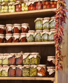 many jars with typical calabrian food such as dried tomato peppers and anchovy very hot