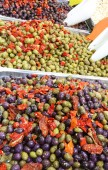 tray filled with black and green olives with peppers for sale in the market stall of a Mediterranean country
