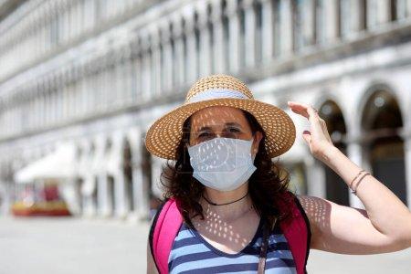 belle femme avec chapeau et masque chirurgical pendant le voyage à Venise en Italie dans la période de l'épidémie du virus Corona