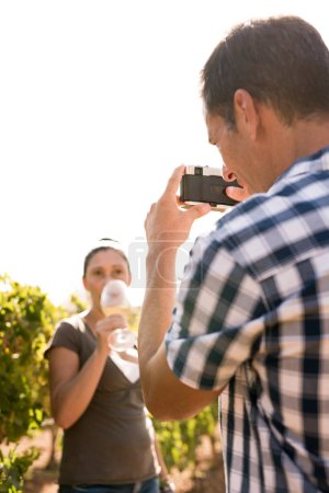 Man taking a photo of a woman drinking wine in a vineyard and she looking at the camera
