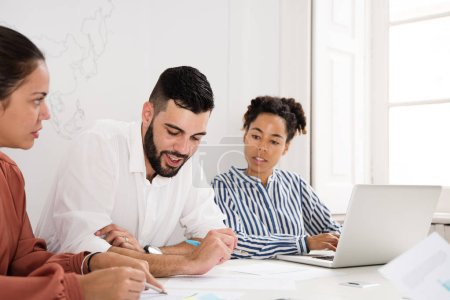 Photo for Two women and a man sitting at a desk holding a meeting, the man is looking down a document - Royalty Free Image