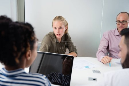 Photo for Business team meeting in an office, the woman in the green shirt is talking to the woman in the stripped shirt - Royalty Free Image