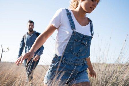 Photo pour Femme qui court dans l'herbe longue avec les bras ouverts et un homme la suit - image libre de droit