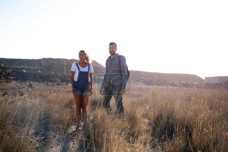 Photo pour Homme et femme regardant la vue comme ils se tiennent sur une plaine herbeuse - image libre de droit