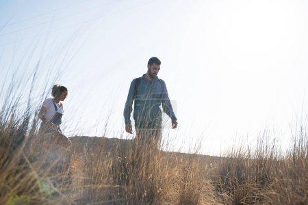 Photo pour Homme et femme marchant dans l'herbe longue avec les montagnes en arrière-plan - image libre de droit