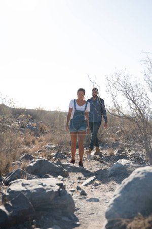Photo pour Couple marchant dans le désert le long d'un chemin parsemé de rochers et d'arbres - image libre de droit