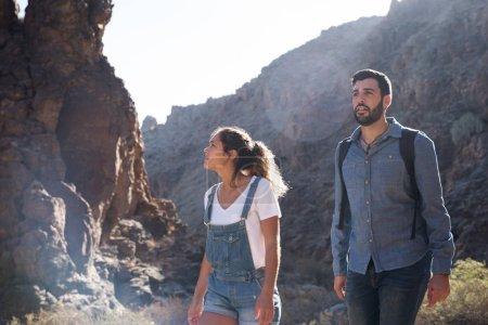 Photo pour Femme et homme marchant sur un sentier de montagne rocheux, il regarde vers l'avenir et elle regarde les formations rocheuses à côté d'elle - image libre de droit