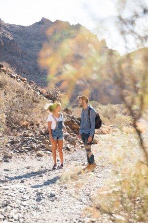 Photo pour Homme et femme au loin debout et parlant sur un chemin rocheux dans le désert - image libre de droit