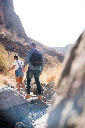 Photo pour Homme et femme marchant sur un sentier rocheux au-dessus des rochers et des pierres et essayant de s'équilibrer, ils sont dans un désert - image libre de droit