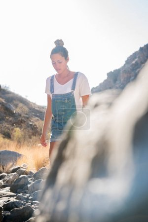 Photo for Woman walking past an outcrop of rocks and foliage on a mountain path as she looks down - Royalty Free Image