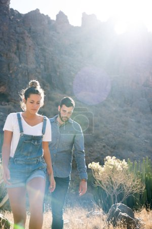 Couple hiking in the mountains as they walk in long grass and bushes, they are both looking down