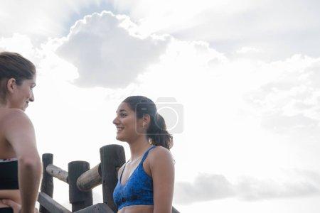 Photo pour Deux coureuses se regardent et se parlent en souriant à la plage - image libre de droit
