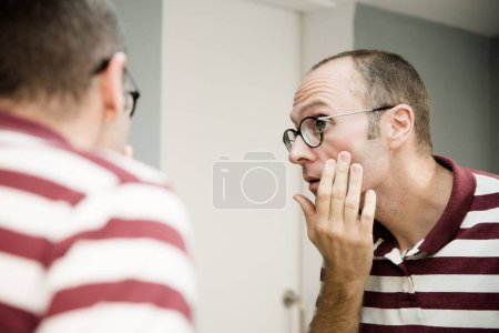 Reflective image of a man looking into a mirror as he touches his cheek and looks to the side