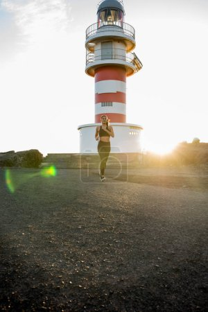 Woman running past a lighthouse as the sun sets in the distance with lens flare on camera