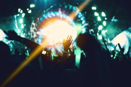 Photo pour Concert de rock avec des gens de silhouettes en geste heureux et en soulevant les mains Cheer up chanteur. Concept de divertissement et les gens. Thème de Singer et le public. Tons de vert et de l'éclairage jaune Orange - image libre de droit