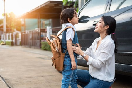 Photo for Mother preparing to send her children back to school at car in morning. Mom say Good bye before school start. Education and Back to school concept. Happy family and preschool student and education - Royalty Free Image