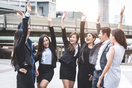 Photo for Portrait of successful group of business people at outdoor urban. Happy businessmen and businesswomen raising hand as team in satisfaction gesture. Successful group of people smiling after achievement - Royalty Free Image