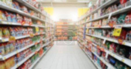 Photo pour Blurry shopping les rayons des supermarchés et grands magasins. Centre commercial produit vitrine passage couvert en face de votre panier - image libre de droit