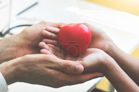 Photo pour Docteur mains tenant et donnant rouge massage coeur aux patients petits enfants pour récupérer de la maladie. Concept d'hôpital et des soins de santé. Réanimation cardio-respiratoire et cardiologie de crise cardiaque et de maladie. Faire un don du coeur - image libre de droit