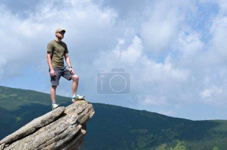 Photo pour Jeune homme au sommet des montagnes - image libre de droit