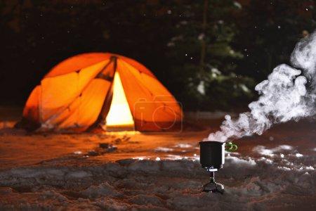 Photo pour Cuisiner la nourriture sur le poêle du camp sur la tente de fond et la forêt de nuit d'hiver - image libre de droit