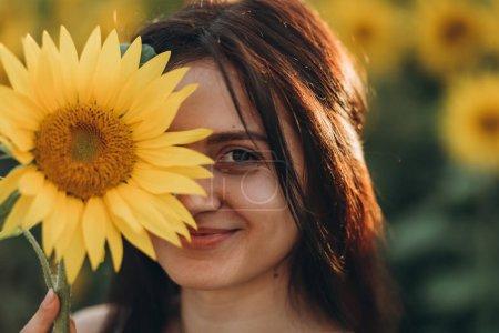 Photo pour Portrait d'une belle femme aux cheveux bruns avec des tournesols - image libre de droit