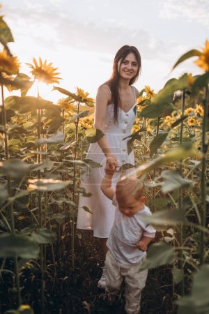 Photo for Mom and son hug, laugh and play in a field of sunflowers. Happy family moments spent in the open air. Mother's Day. - Royalty Free Image
