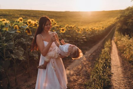 Photo for Mother and little son having fun together in sunflower field - Royalty Free Image