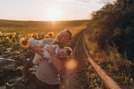 Photo for Young father and son having fun together at summer sunflowers field - Royalty Free Image