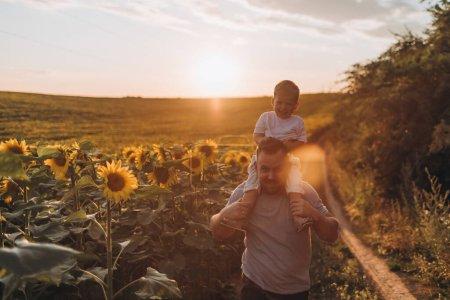 Photo pour Jeune père et fils s'amusent ensemble au champ de tournesols d'été - image libre de droit