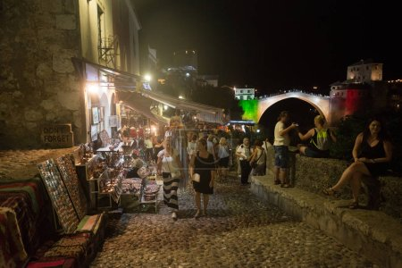 Photo for Mostar, Bosnia and Herzegovina, circa july 2016: Tourists and locals walking on Old bridge and on streets of the town of Mostar at night. Included to the UNESCO heritage - Royalty Free Image