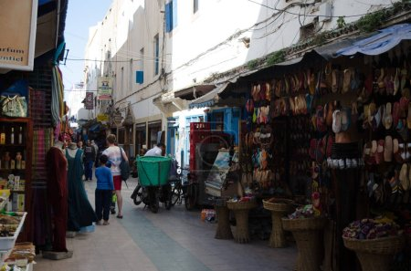 Foto de ESSAOUIRA, MOROCCO - CIRCA MAY 2013: typical street of Essaouira with coffees and restaurants. Essaouira is one of the most touristic place in Morocco for his beautiful beaches - Imagen libre de derechos