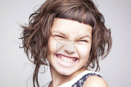 Porträt eines glücklich lächelnden kleinen Mädchens mit stilvoller Frisur isoliert auf weißem Hintergrund, Nahaufnahme