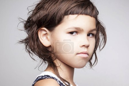 portrait of serious little girl with stylish hairdo looking at camera isolated on white background, close-up