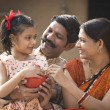 Indian parents with daughter holding piggy bank wh...