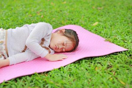 Little Asian child girl sleeping on pink mattress in green grass lawn at summer park garden.
