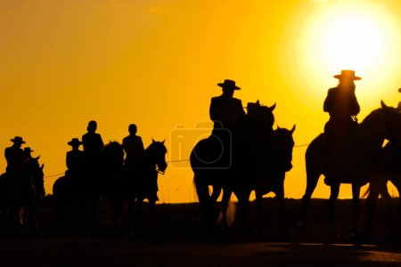 Silhouettes of cowboys in hats on horses