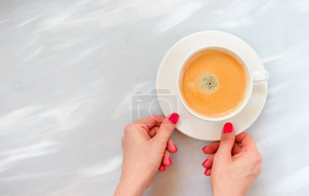 Photo for Woman hands holding coffee mug or cup on colorful table. Photograph taken from above, top view with copy space - Royalty Free Image
