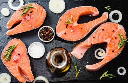 Photo for Two salmon steak, butter, pepper and salt, lemon, herbs border ,place for text on wooden rustic background top view - Royalty Free Image